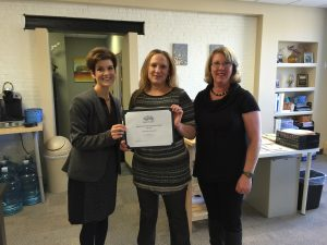 Stacey Bruzzese, President/CEO(left) and Melissa Seavey (right) present the Business of the Month Award to Angela Orben, Secretary of the Board of Directors for the Steve Lyons Fund organization.