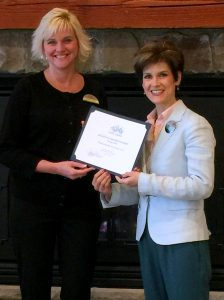 # Photo Caption: Kristin Perry, CFO at Atkinson Resort & Country Club accepts the Business of the Month Award from Chamber President/CEO, Stacey Bruzzese