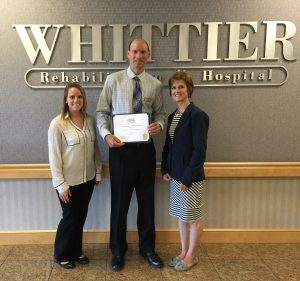 Kelly Michal, Membership Coordinator (left) and Stacey Bruzzese, President & CEO (right) of the Greater Haverhill Chamber present the Business of the Month Award to Bob Iannacco, Administrator of Whittier Rehabilitation Hospital