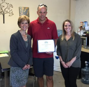 Chamber President, Stacey Bruzzese (left) and Membership Coordinator, Kelly Michal (right) present the Business of the Month Award to company owner, Doug Hall (center)